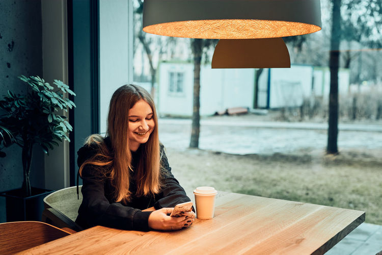 Portrait of smiling woman sitting by coffee at cafe table
