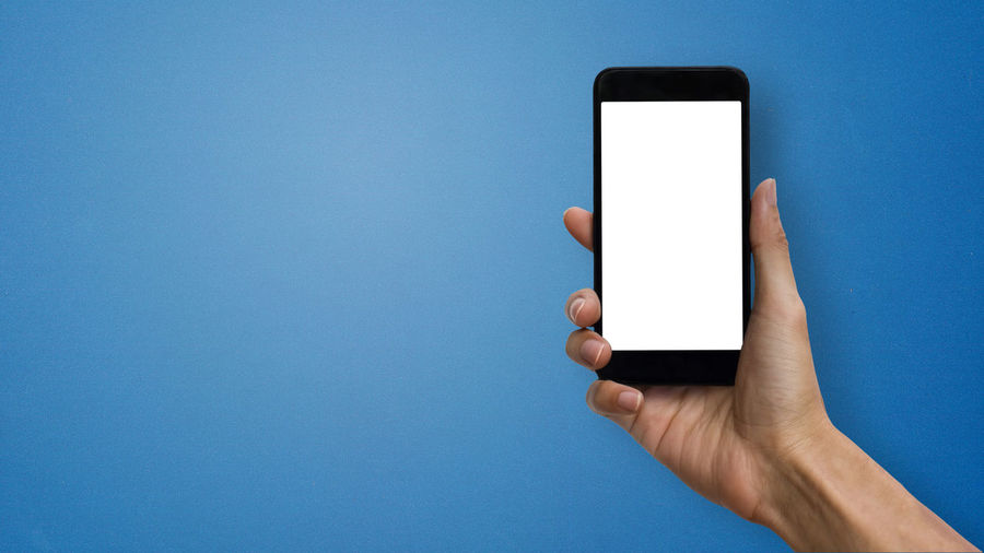 Midsection of person holding smart phone against blue background