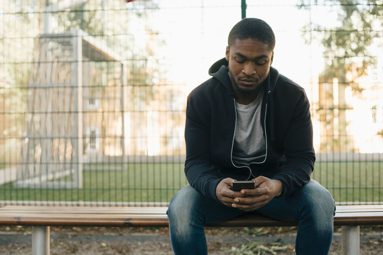 Young man looking away while sitting on mobile phone