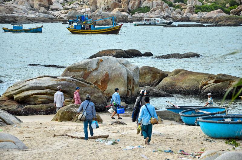 People walking on rock by sea