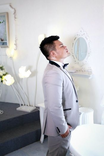 Side view of bridegroom wearing gray suit standing with eyes closed against wall
