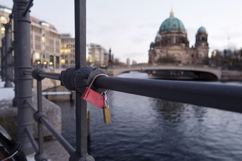 Close-Up Of Padlocks On Railing Against Bridge In City