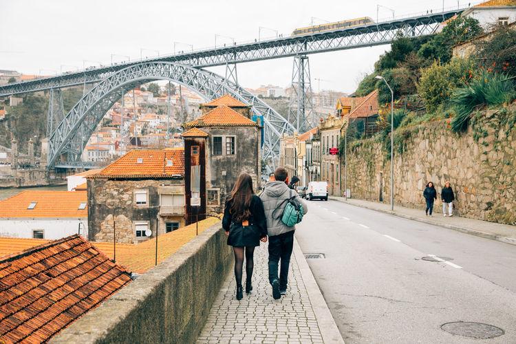 Rear view of couple walking on footpath towards dom luis i bridge