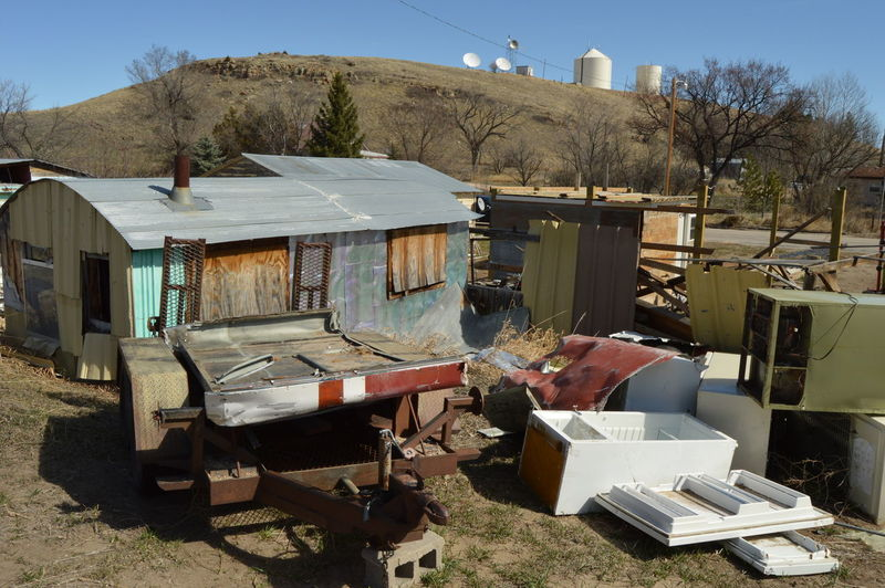 Junkyard and house against mountain