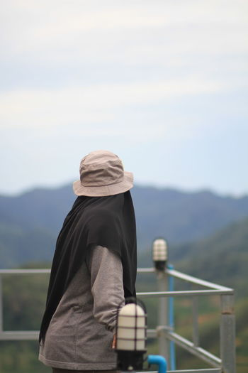 Side view of woman standing by railing against mountain