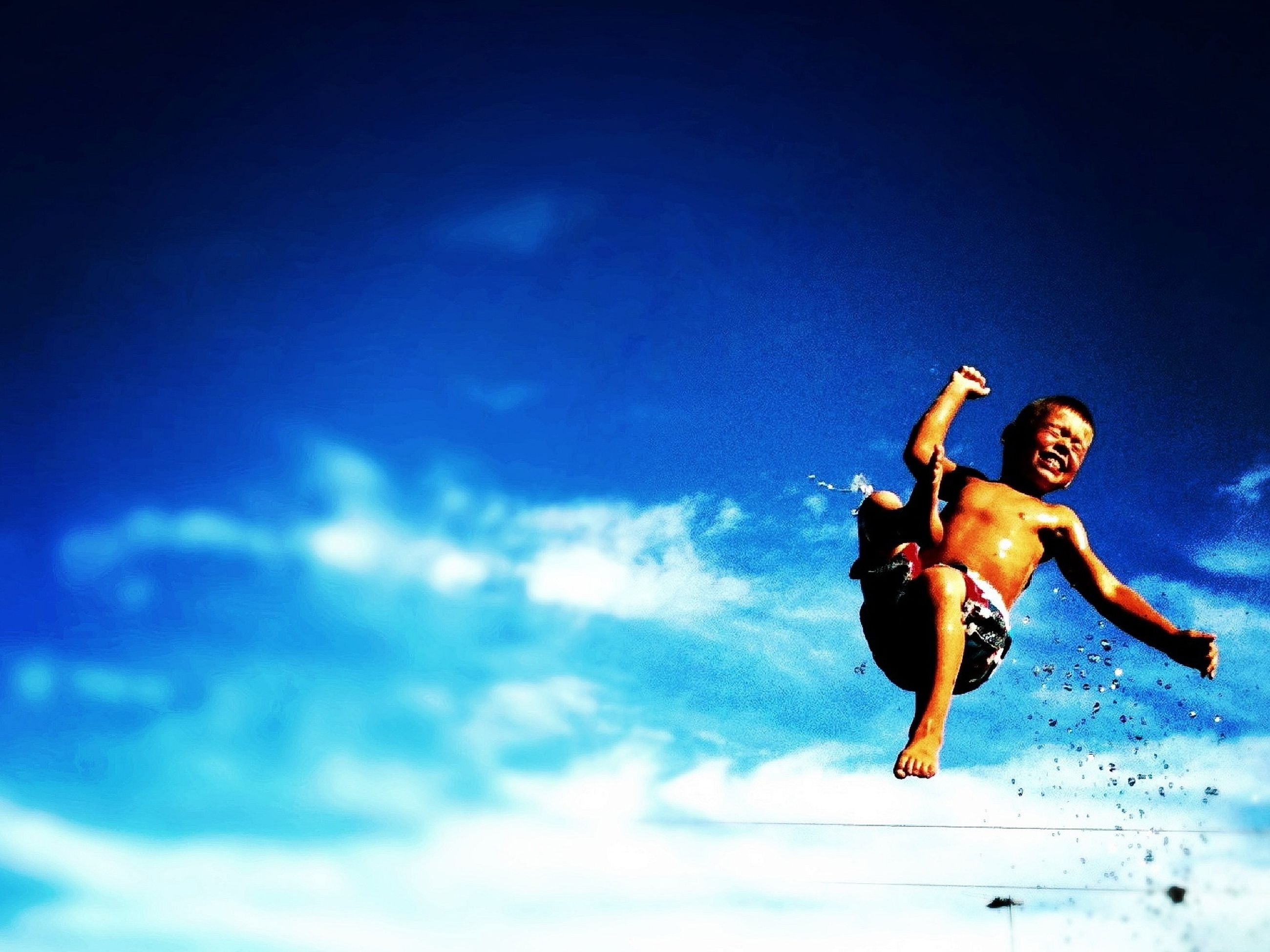 low angle view, sky, leisure activity, human representation, lifestyles, men, skill, mid-air, full length, art, extreme sports, blue, creativity, art and craft, cloud - sky, adventure, fun
