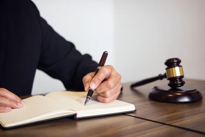 Lawyer Barrister Book Consultant Fairness Gavel Hand Holding Human Body Part Human Hand Indoors  Judge Judgement Legal Legislation One Person Paper Pen Publication Signing Studying Verdict Women Writing Writing Instrument