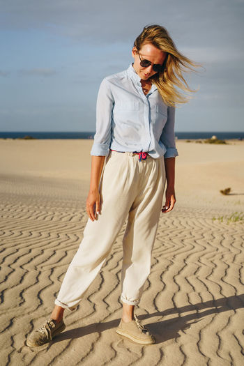 Stylish woman dressed in light clothes standing on blue stairs Desert Dunes Sand Landscape Arid Climate Wild Hot Sandy Corralejo Natural Nature Fuerteventura Canary Islands Woman Female Girl person Young Free Freedom Waiting Background Model Posing Traveler Caucasian Sunset Evening Golden Alone Single Wanderer Wandering Dreaming Thinking Travel Vacation Adventure Explore