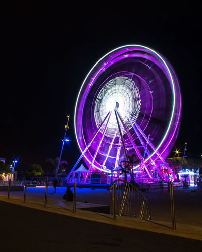 Illuminated ferris wheel against clear sky at night