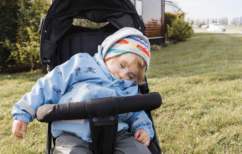 Cute Boy Sleeping On Baby Stroller At Lawn