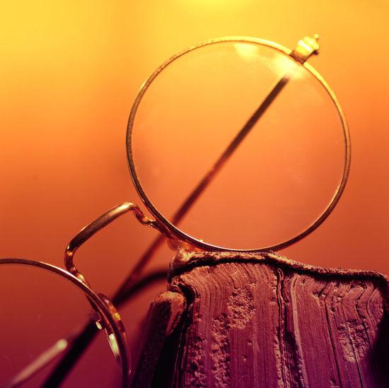 Close-up of eyeglasses against orange background