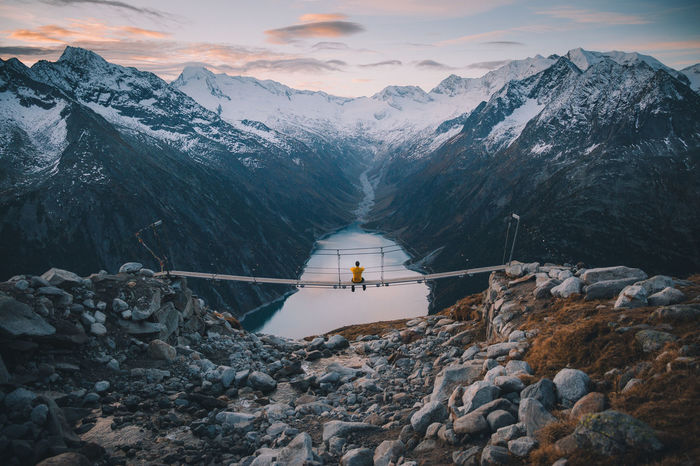 Rear view of man sitting on bridge over river against mountain