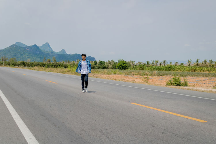 Rear view of man standing on road