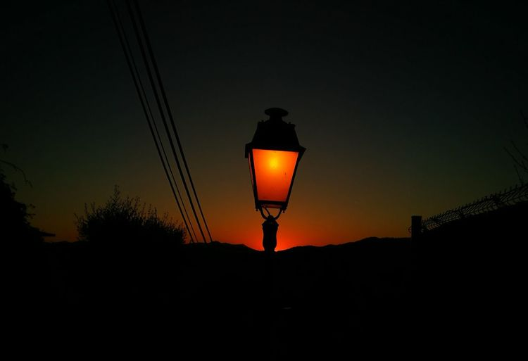 Low angle view of illuminated lamp at sunset