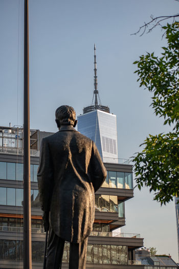 Rear view of statue against sky in city