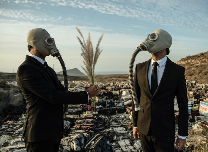 Mature men wearing gas mask standing outdoors
