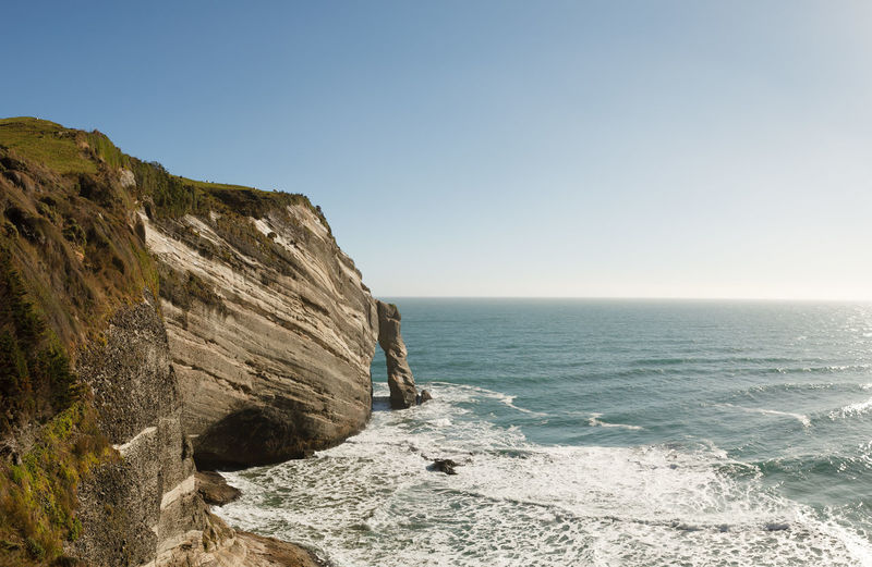Scenic view of cliff and sea against clear sky
