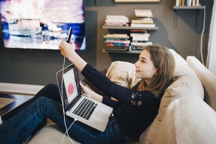 Full length of girl using mobile phone at home