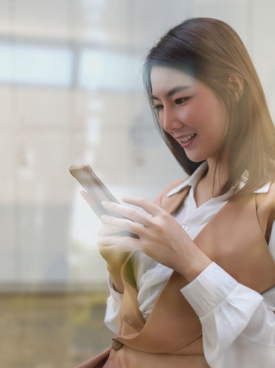 Young smiling woman using smart phone sitting at restaurant