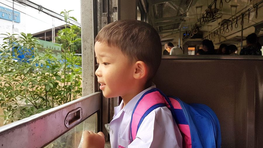 Side view of male student looking through window in train