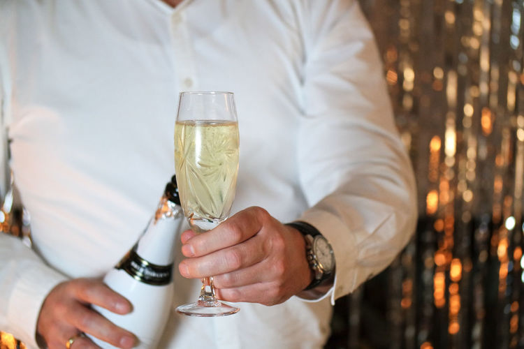 Glitter & Sparkle Adult Alcohol Bokeh Background Bokeh Lights Celebration Champagne Champagne Flute Close-up Drink Drinking Drinking Glass Gold Colored Happy New Year Holding Human Hand Indoors  Men Midsection New Years Eve Night Refreshment Wine Wineglass