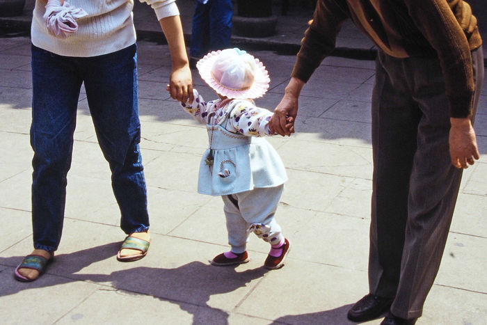 People Real People Men Girls Walking Love Women Shadow Boys Sunlight Child Mother Day Holding Hands Standing Outdoors Childhood Daughter Bonding Father Togetherness Adult Lifestyles Low Section One Child Policy