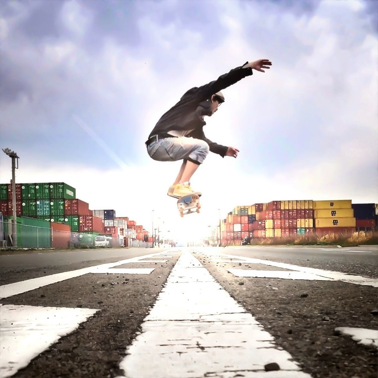 Low angle view of young man skateboarding on road