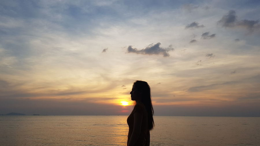 Side view of woman standing by sea against sky during sunset