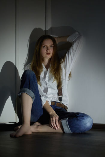 Portrait of young woman sitting against wall at home