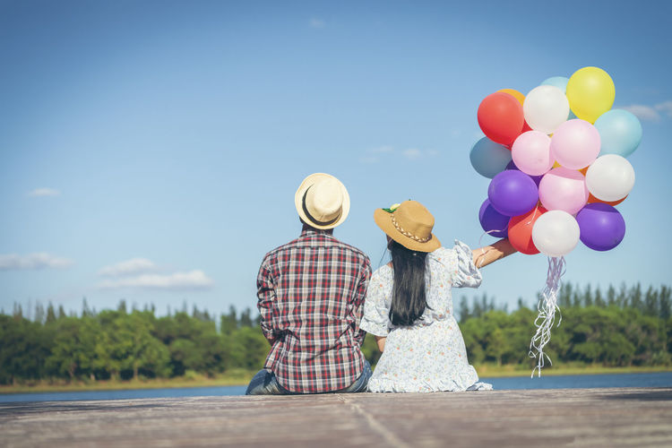 Rear view of couple with balloons against sky