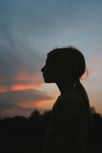 Portrait of silhouette woman standing against sky during sunset