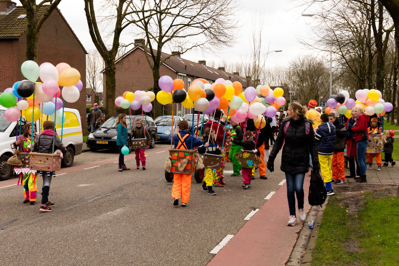 balloon, large group of people, multi colored, celebration, real people, tree, day, outdoors, bare tree, enjoyment, clown, fun, built structure, men, building exterior, helium balloon, togetherness, full length, architecture, women, sky, bubble wand, adult, people, adults only