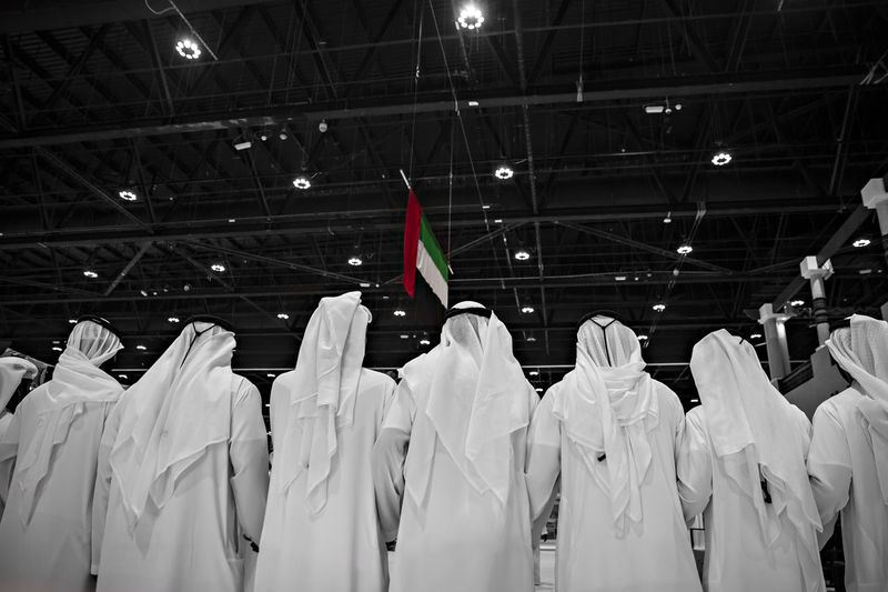 Rear view of men wearing white traditional clothing with united arab emirates flag hanging from ceiling in background