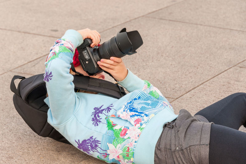 Low section of woman photographing camera