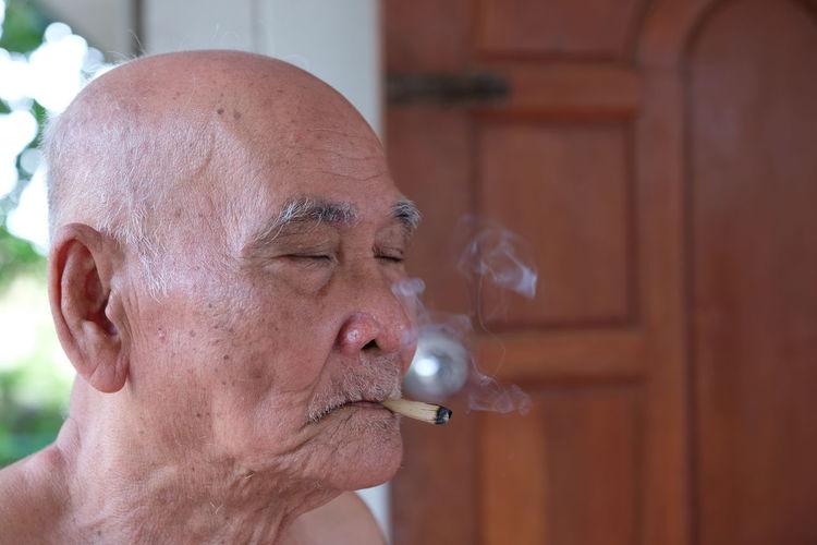 Shirtless senior man smoking cigarette while sitting outdoors