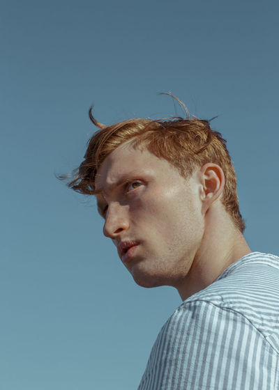 Myroslav #16 The result of a spontaneous hour-long shoot during the first meeting with the person, Editorial Fashion The Week on EyeEm TheWeekOnEyeEM Blue Casual Clothing Clear Sky Editorial Photography Fashion Editorial Fashion Photography Hairstyle Headshot Leisure Activity Looking Away Model Test Shoot Portrait Real People Redhead Young Adult The Fashion Photographer - 2018 EyeEm Awards