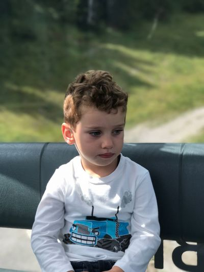 Cute boy relaxing in vehicle