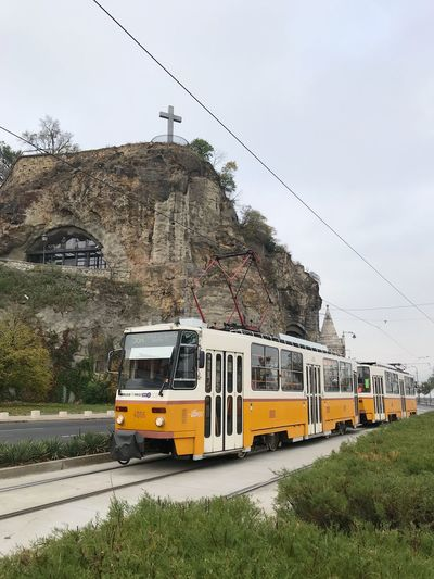 Travel Yellow Tram Wall Budapest Hungary Mode Of Transportation Transportation Sky Public Transportation Nature Land Vehicle Rail Transportation Cable Car No People Architecture Outdoors Day Railroad Track Track Train Cable Train - Vehicle Plant Tree Land