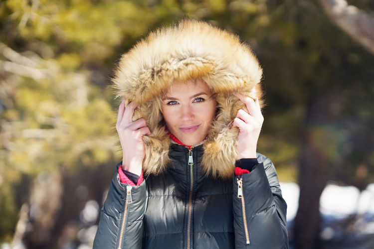 Portrait of smiling young woman standing outdoors during winter