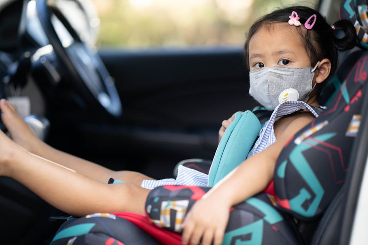 Cute little girl wearing healthy face mask prevent virus and pm2.5 in carseat