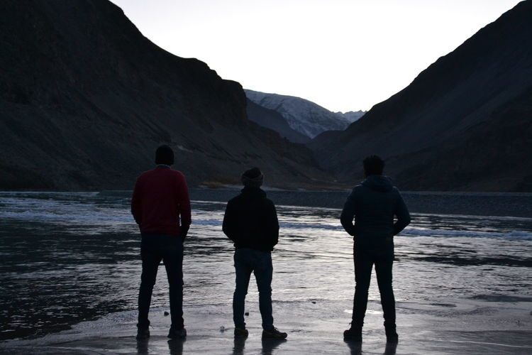 Rear view of men standing by lake against mountains