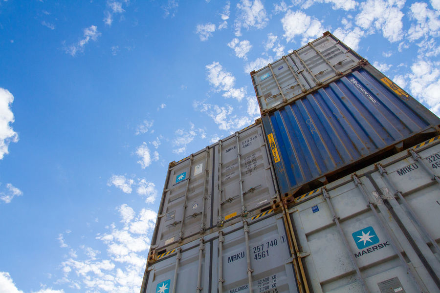 Shipping and cargo containers stacked high in a freight yard or rail port. Boxes Business Cargo Commerce Container Delivery Dock Docks Freight Import Important Industry Logistics Port Sea Shipping  Shipping Containers Stack Storage Trade Transportation Warehouse