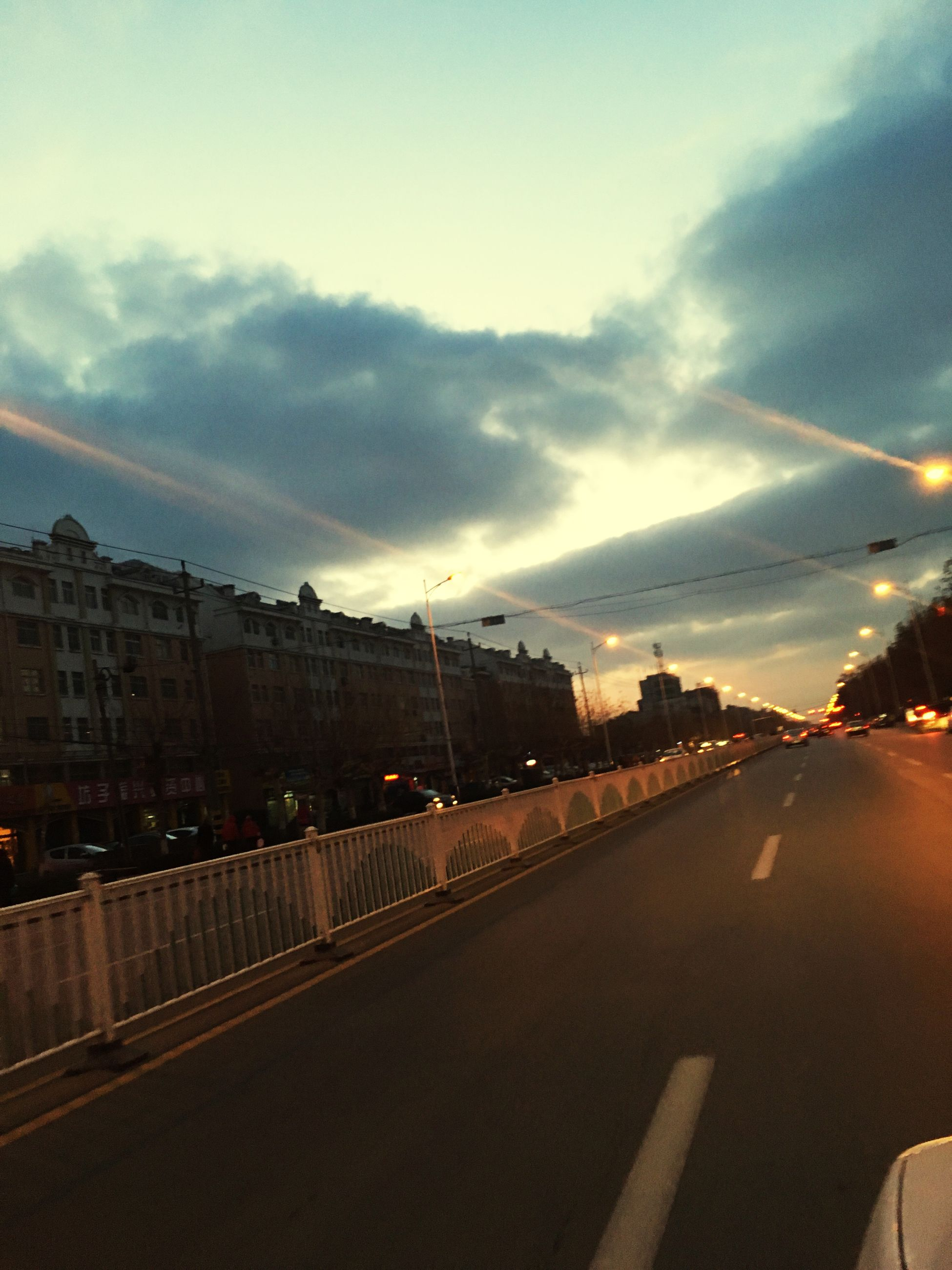 transportation, sky, road, road marking, cloud - sky, the way forward, car, building exterior, built structure, architecture, mode of transport, city, street, land vehicle, dusk, street light, diminishing perspective, on the move, city life, illuminated
