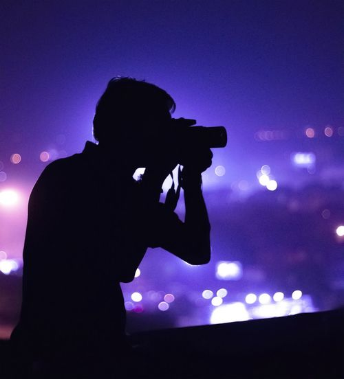 Side view of a silhouette male photographer