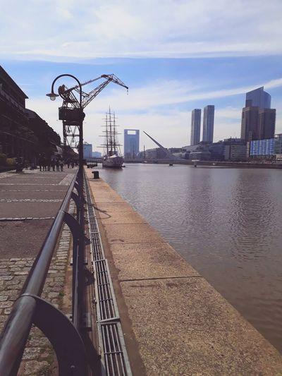 Bridge over river by city buildings against sky