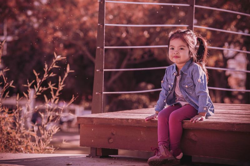 Full length of girl sitting on wooden walkway