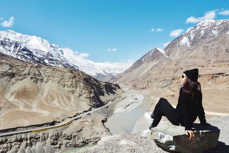 Woman sitting on snowcapped mountain against sky