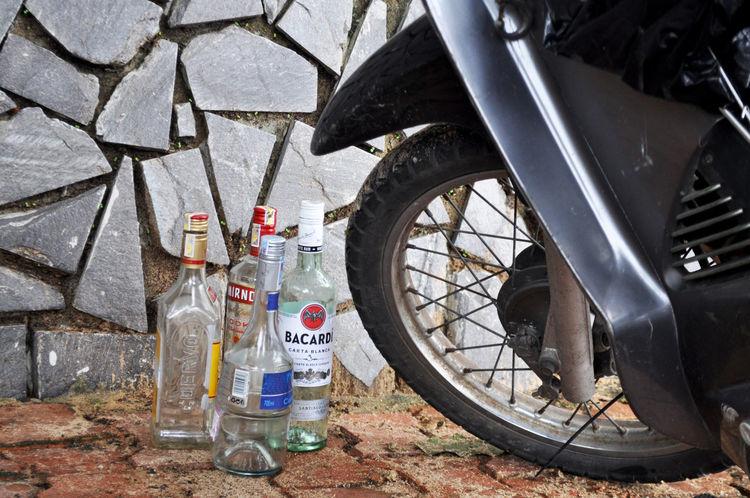 Empty spirit bottles beside motorcycle parked on footpath in Da Nang, Vietnam. Alcohol Booze Da Nang Day Drinking Empty Bottles Footpath Motorcycles Outdoors Parked Rock Walls Spirits Spokes Tire Transportation Vietnam Wheels