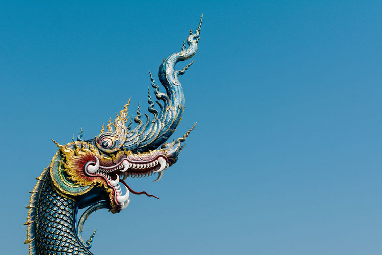 Low angle view of dragon statue at wat rong khun against clear sky