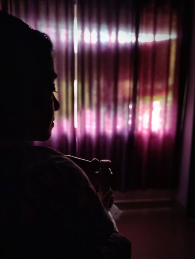 Woman by curtain at home